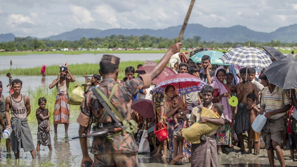 In this Tuesday, Oct. 17, 2017, file photo, a Bangladesh border guard soldier stops newly arrived Rohingya Muslims, who crossed over from Myanmar into Bangladesh, from moving ahead towards refugee camps, at Palong Khali, Bangladesh. Thousands more Rohingya Muslims are fleeing large-scale violence and persecution in Myanmar and crossing into Bangladesh, where more than half a million others are already living in squalid and overcrowded camps, according to witnesses and a drone video shot by the U.N. office for refugees. (AP Photo/Dar Yasin, File)