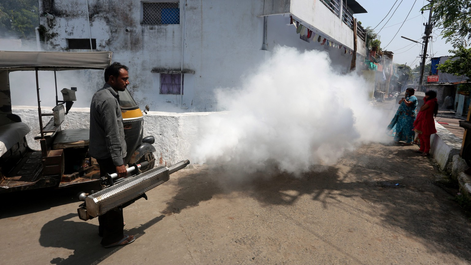 epa04918279 Municipal Corporation sanitation workers fumigate an area as part of an anti-malaria fumigation drive to curb breeding sites for mosquitoes causing dengue and malaria after the dengue outbreak in Bhopal, India, 07 September 2015. Dengue has spread widely in Bhopal with some 300 people suffering from the mosquito-borne tropical disease.  EPA/SANJEEV GUPTA