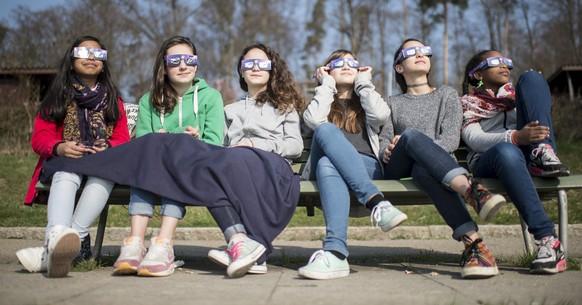 Junge Frauen verfogen mit Schutzbrillen das Naturspektakel der partiellen Sonnenfinsternis am Freitag, 20. Maerz 2015 in Zuerich. Am Himmel ueber Westeuropa ist heute eine partielle Sonnenfinsternis zu beobachten. Seit 9.30 Uhr schiebt sich der Mond von der Erde aus gesehen vor die Sonne. Der Hoehepunkt der partiellen Sonnenfinsternis - die groesste Abdeckung der Sonne und damit der staerkste Grad der Verdunkelung - wird etwa eine Stunde spaeter erwartet. Kurz vor Mittag ist die Sonne dann wieder ganz am Himmel zu sehen.(KEYSTONE/Ennio Leanza)  Young women watch the spectacle of a partial solar eclipse in Zurich, Switzerland, Friday, 20 March 2015. A Partial Solar Eclipse is seen today in Europe, northern and eastern Asia and northern and western Africa. The eclipse starts at 07:41 UTC and ends at 11:50 UTC. (KEYSTONE/Ennio Leanza)