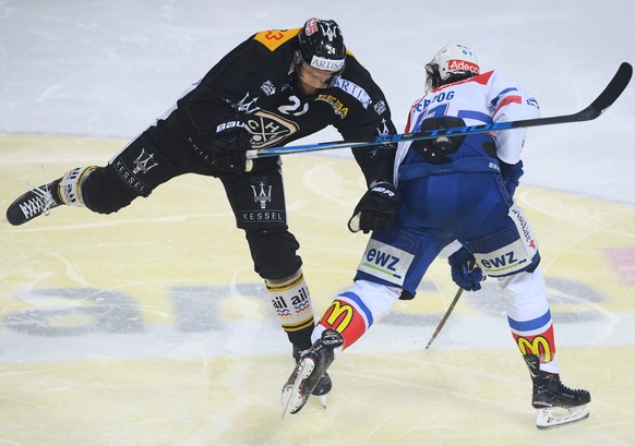 LuganoÕs player Jani Lajunen, left, fights for the puck with Zurich's player Fabrice Herzog, right, during the first match of the playoff final of National League between HC Lugano and ZSC lions, at the ice stadium Resega in Lugano, on Thursday, April 12, 2018. (KEYSTONE/Ti-Press/Alessandro Crinari)