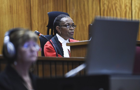 epa04395125 Judge Thokozile Masipa reads her verdict as South African Paralympic athlete Oscar Pistorius (not pictured) sits in the dock during the verdict in his murder trial, Pretoria, South Africa, 11 September 2014. Pistorius awaits his verdict after standing trial from 03 March 2014 for the premeditated murder of his model girlfriend Reeva Steenkamp in February 2013.  EPA/PHILL MAGAKOE / POOL