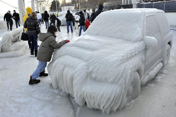 Молодой человек идет вдоль покрытой льдом машины на набережной со льдом на Женевском озере в Версуа, Швейцария, в воскресенье, 5 февраля 2012 года. В Европе наступили холодные периоды, когда температура резко упала ниже нуля. (ТРАПЕЦИЯ / Мартиал Трезини)