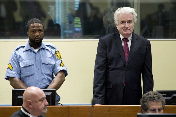 epa07450691 Former Bosnian Serb leader Radovan Karadzic (R) enters the court room of the Former Bosnian Serb leader Radovan Karadzic (R) enters the court room of the International Residual Mechanism for Criminal Tribunals in The Hague, Netherlands, 20 March 2019. Nearly a quarter of a century since Bosnia's devastating war ended, Karadzic is set to hear the final judgment on whether he can be held criminally responsible for unleashing a wave of murder and destruction. United Nations appeals judges will on Wednesday rule whether to uphold or overturn Karadzic's 2016 convictions for genocide, crimes against humanity and war crimes, as well as his 40-year sentence.  EPA/PETER DEJONG / POOL
