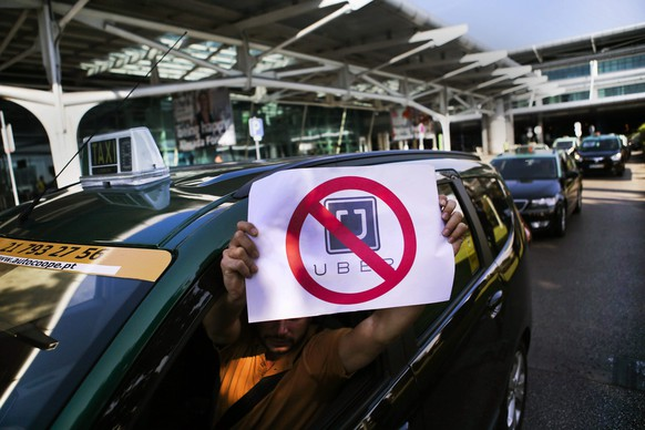 epa04920181 A taxi driver hold a crossed out Uber sign during a protest action in Lisbon, Portugal, 08 September 2015. More than a thousand taxi drivers protested in Lisbon against ride-sharing company Uber, blocking roads and stalling traffic during morning rush hour as tensions rise in the city over the mobile app ride service.  EPA/MARIO CRUZ