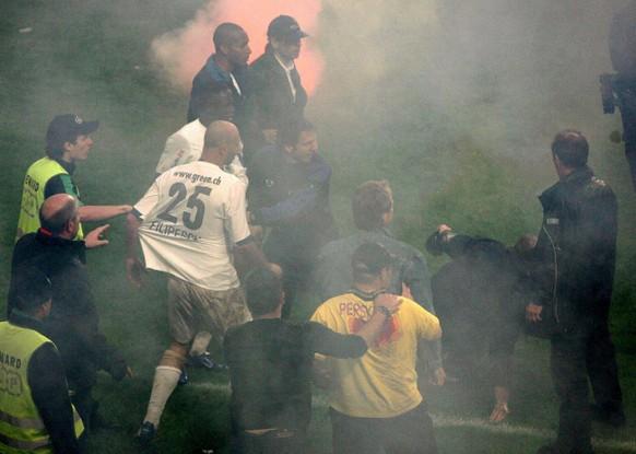 Die Zuercher Spieler Iulian Filipescu, Nr. 25, und Alhassane Keita, links daneben, werden taetlich angegriffen nach dem Fussball Meisterschaftsspiel der Super League zwischen dem FC Basel und dem FC Zuerich am Samstag, 13. Mai 2006, in Basel. (KEYSTONE/Patrick Straub)