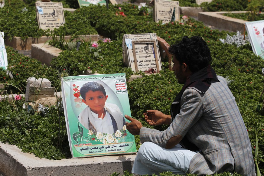 epa05345243 A Yemeni sits nearby the grave of Yemeni child Bilal al-Asadi who was killed in a Saudi-led airstrike hit his family house, on International Day of Innocent Child Victims of Aggression, in Sana'a, Yemen, 04 June 2016. According to reports, the UN has added the Saudi-led coalition to a blacklist of armed groups who violate the rights of children, holding Saudi Arabia responsible for 60 percent of child casualties in the 14 month-conflict in Yemen.  EPA/YAHYA ARHAB