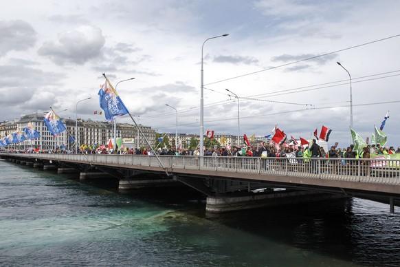 Des manifestants avec des pancartes et des drapeaux defilent sur le pont du Mont-Blanc, lors du defile du 1er mai - Fete du Travail, ce mardi 1 mai 2018 a Geneve. A Geneve, pres de 2'000 personnes ont participe au traditionnel cortege du 1er mai place, cette annee, sous le signe de l'egalite salariale. D'autres revendications pour plus de justice sociale se sont aussi exprimees lors du defile. (KEYSTONE/Salvatore Di Nolfi)