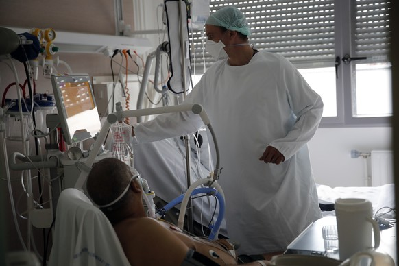A member of the medical staff tends to a patient affected by the COVID-19 virus in the ICU unit at the Charles Nicolle public hospital, Thursday, April 15, 2021 in Rouen, France. A renewed crush of COVID-19 cases is again forcing intensive care units across France to grapple with the macabre mathematics of how to make space for thousands of  critically ill patients (AP Photo/Christophe Ena)