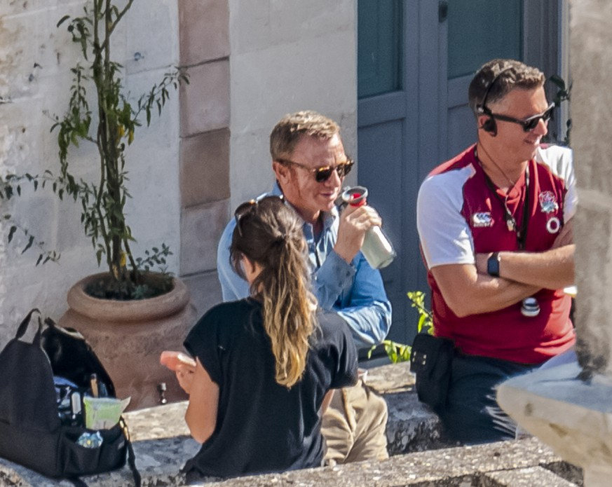 In this Sept. 12, 2019 photo, actor Daniel Craig, center, sips a drink during a break on the set of the latest James Bond movie 'No time to die' in Matera, southern Italy. The film is due out in spring 2020. (AP Photo/Fabio Dell'Aquila) Daniel Craig