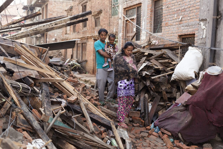 epa04752567 Local people walks in the rubble of collapsed houses in Kritipur, on the outskirts of Kathmandu, as Nepal tries to recover from two powerful earthquakes, 17 May 2015. The death toll for 12 May's 7.3 magnitude quake rose to 117, authorities said, separate from the 8,202 victims claimed by the April 25 earthquake. Affected children were 'facing an unprecedented emotional toll' from the double trauma of two natural disasters in a short period of time, the United Nations warned.  EPA/HEMANTA SHRESTHA