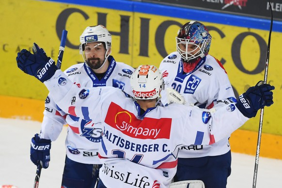 Zurich's goalkeeper Lukas Flueeler, right,  celebrates the 0-1 victory with Zurich's player Patrick Geering, left, and Zurich's player Chris Baltisberger, center, during the first match of the playoff final of the National League between HC Lugano and ZSC Lions, at the ice stadium Resega in Lugano, on Thursday, April 12, 2018. (KEYSTONE/Ti-Press/Alessandro Crinari)