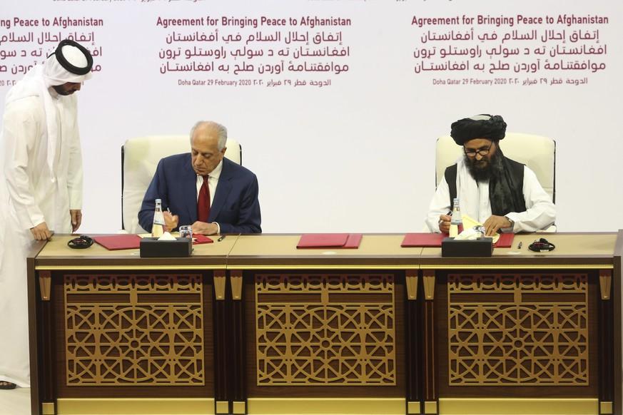 U.S. peace envoy Zalmay Khalilzad, left, and Mullah Abdul Ghani Baradar, the Taliban group's top political leader sign a peace agreement between Taliban and U.S. officials in Doha, Qatar, Saturday, Feb. 29, 2020. The United States is poised to sign a peace agreement with Taliban militants on Saturday aimed at bringing an end to 18 years of bloodshed in Afghanistan and allowing U.S. troops to return home from America's longest war. (AP Photo/Hussein Sayed)