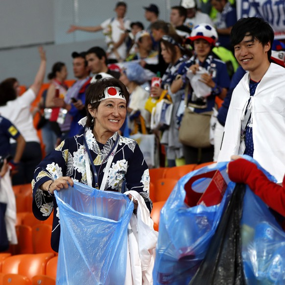 epa06836994 Supporters of Japan pull out garbage bags to pick up the trash in the stands after the FIFA World Cup 2018 group H preliminary round soccer match between Japan and Senegal in Ekaterinburg, Russia, 24 June 2018.(RESTRICTIONS APPLY: Editorial Use Only, not used in association with any commercial entity - Images must not be used in any form of alert service or push service of any kind including via mobile alert services, downloads to mobile devices or MMS messaging - Images must appear as still images and must not emulate match action video footage - No alteration is made to, and no text or image is superimposed over, any published image which: (a) intentionally obscures or removes a sponsor identification image; or (b) adds or overlays the commercial identification of any third party which is not officially associated with the FIFA World Cup)  EPA/FRANCIS R. MALASIG   EDITORIAL USE ONLY