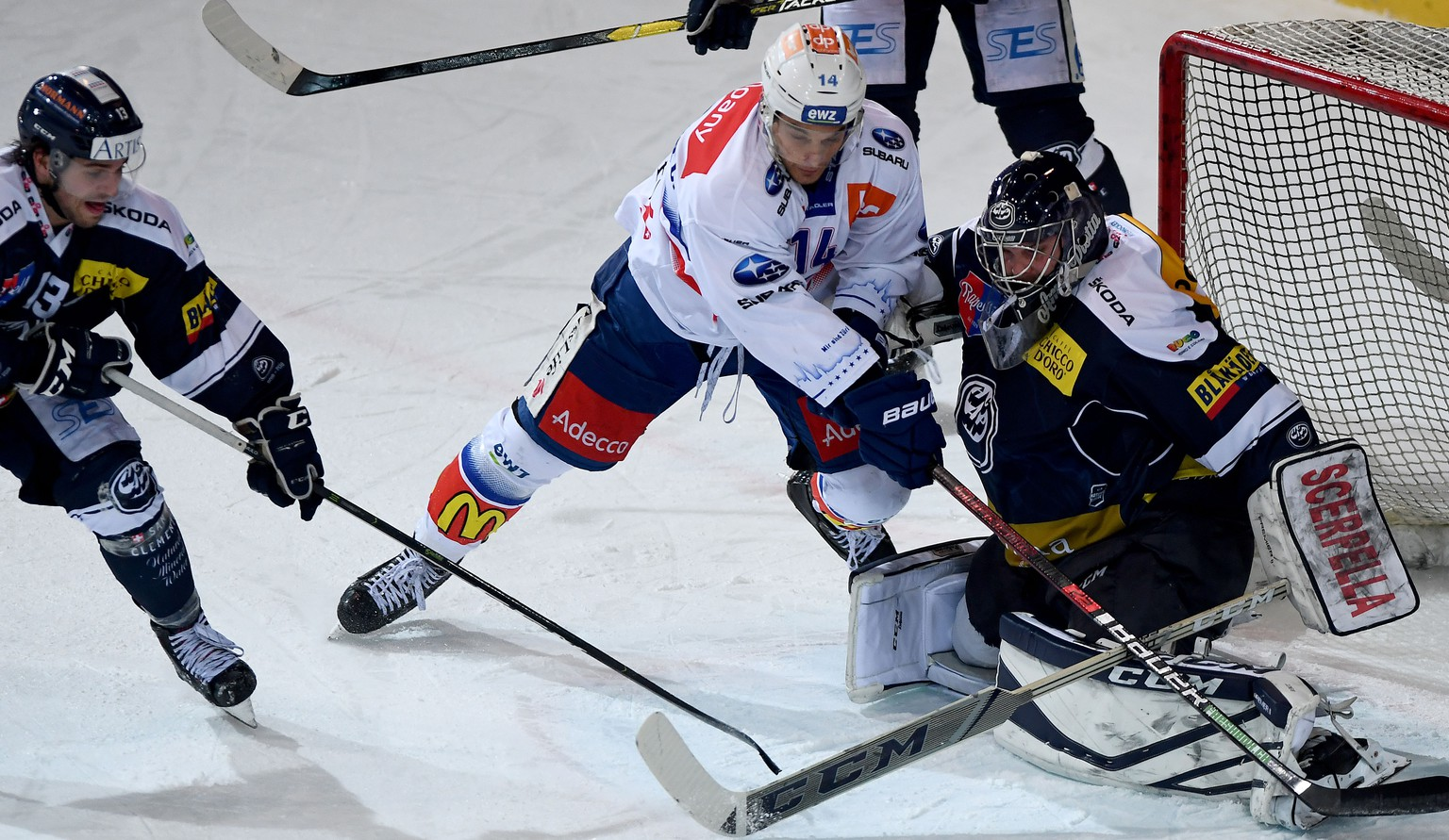 From left  Ambri's player Marco Müller, Zsc'player Chris Baltisberger and Ambri's goalkeeper Benjamin Conz, during the preliminary round game of National League A (NLA) Swiss Championship 2018/19 between HC Ambri Piotta and ZSC Lions, at the ice Stadium Valascia in Ambri, Switzerland, Saturday, January 26, 2019. (KEYSTONE/Ti-Press/Samuel Golay)