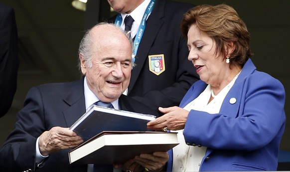 epa04277695 FIFA President Sepp Blatter (L) distributes books on the stands prior the FIFA World Cup 2014 group D preliminary round match between Italy and Uruguay at the Estadio Arena das Dunas in Natal, Brazil, 24 June 2014. (RESTRICTIONS APPLY: Editorial Use Only, not used in association with any commercial entity - Images must not be used in any form of alert service or push service of any kind including via mobile alert services, downloads to mobile devices or MMS messaging - Images must appear as still images and must not emulate match action video footage - No alteration is made to, and no text or image is superimposed over, any published image which: (a) intentionally obscures or removes a sponsor identification image; or (b) adds or overlays the commercial identification of any third party which is not officially associated with the FIFA World Cup)  EPA/KAMIL KRZACZYNSKI   EDITORIAL USE ONLY