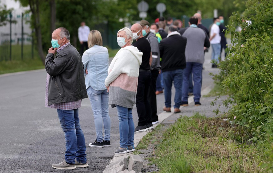 epa08413193 Employees queue for a coronavirus test at a testing station on the factory premises of the Westfleisch meat processing company in Hamm, Germany, 10 May 2020. A large-scale corona test was started in Hamm on more than 1,000 'Westfleisch' employees. The reason for the action by the city of Hamm was the reports from the cities of Coesfeld and Oer-Erkenschwick, where hundreds of employees of 'Westfleisch' slaughterhouses were infected. The German Government and local authorities had recently relaxed measures which should have curbed the spread of the coronavirus SARS-CoV-2, which causes COVID-19 disease.  EPA/FRIEDEMANN VOGEL