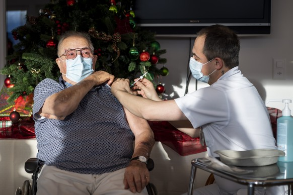 Un infirmier du Chuv donne la premiere dose du vaccin Pfizer-BioNTech au premier resident vaudois, Albert Favre, a l'occasion du lancement de la vaccination contre le Sars-Cov-2 dans l'EMS La Maison du Pelerin dans le canton de Vaud lors de la crise du Coronavirus (Covid-19) le mercredi 30 decembre 2020 au Mont-Pelerin sur la commune de Chardonne. (KEYSTONE/POOL/Jean-Christophe Bott)