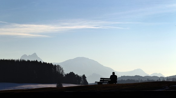 In this Monday March 9, 2015 picture a man enjoys the panorama at Lake Illasbergsee  near the Bavarian  village of Rosshaupten, Germany.  (AP Photo/dpa,Karl-Josef Hildenbrand)