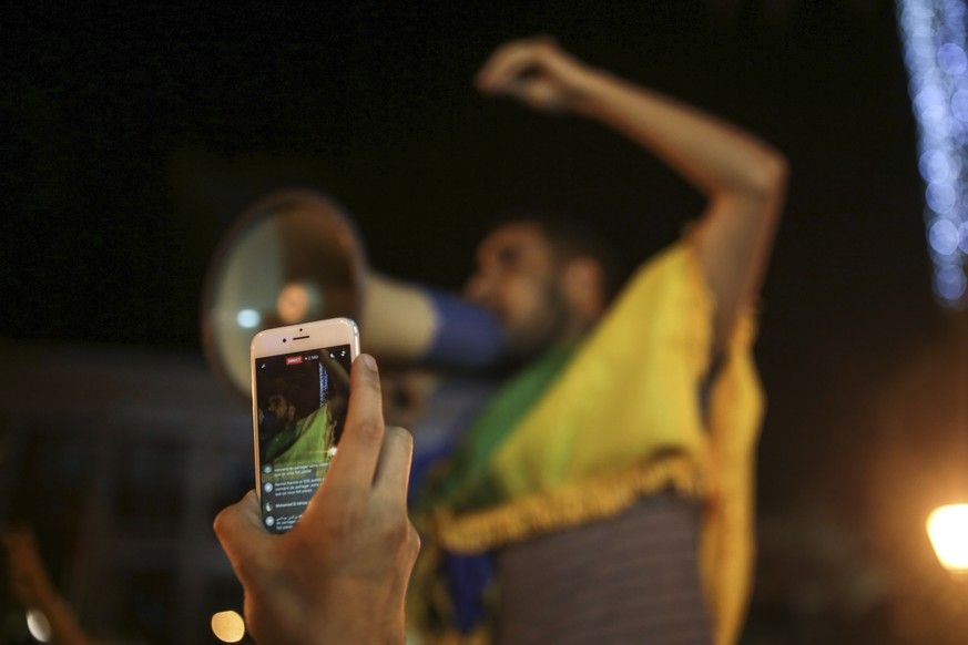 A man broadcasts via Facebook during a demonstration in support of ongoing anti-government protests taking place in the northern Rif region, in Rabat, Morocco, Monday, May 29, 2017. Protests erupted in the northern town of Hoceima last year after the gruesome death of a fisherman, and have now developed into a social and economic movement. (AP Photo/Mosa'ab Elshamy)