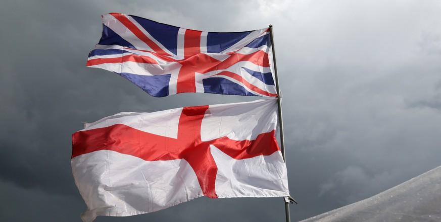 The flag of the United Kingdom of Great Britain and Northern Ireland, top, and the flag of England fly above a souvenir stand on Westminster Bridge following yesterday's EU referendum result, London, Saturday, June 25, 2016. Britain voted to leave the European Union after a bitterly divisive referendum campaign. (AP Photo/Tim Ireland)