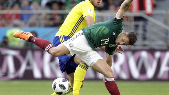FILE - In this Wednesday, June 27, 2018 file photo Sweden's Andreas Granqvist, rear, and Mexico's Javier Hernandez, front, challenge for the ball during the group F match between Mexico and Sweden, at the 2018 soccer World Cup in the Yekaterinburg Arena in Yekaterinburg , Russia. FIFA has fined Sweden's soccer federation 70,000 Swiss francs ($70,750) for players wearing unapproved branded clothing. FIFA says the Sweden team defied requests