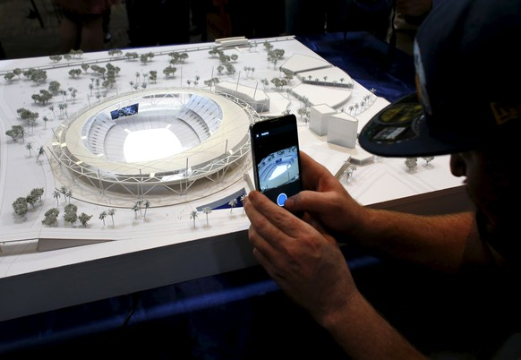 A football fan takes a picture after the San Diego's Citizens Stadium Advisory Group unveiled their plan for building a new $1.1 billion NFL football stadium in San Diego, California May 18, 2015. The San Diego Chargers have announced plans to leave the city unless they can come to terms on the building of a new stadium.     REUTERS/Mike Blake