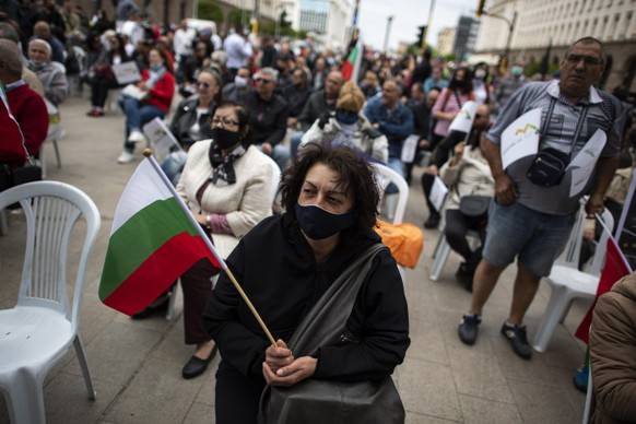 epa08439149 A woman wearing a face mask holds up a Bulgarian national flag during an anti-government protest in front of the building of the Council of Ministers in Sofia, Bulgaria 23 May 2020. Hundreds of people took part in the demonstration by sitting on plastic chairs to maintain the minimum safety distance amid the ongoing pandemic of the COVID-19 disease caused by the SARS-CoV-2 coronavirus. Organized by the 'Izpravi se.BG' civic platform, the protest targeted the government of Prime Minister Boyko Borissov, calling for his resignation while clamoring against the authorities' lack of a clear road map for dealing with the hike in the average price of public utilities, rising unemployment and bankruptcies of small and medium-sized businesses.  EPA/VASSIL DONEV