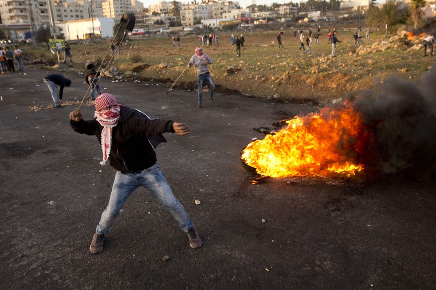 Palestinian protesters throw stones at Israeli troops during clashes following a demonstration to demand the release of bodies of Palestinian attackers by held by Israeli authorities, in the West Bank city of Ramallah, Sunday, Nov. 29, 2015. (AP Photo/Majdi Mohammed)