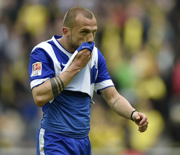 Berlin's John Heitinga from the Netherlands leaves the pitch disappointed after losing the German first division Bundesliga soccer match between Borussia Dortmund and Hertha BSC Berlin in Dortmund, Germany, Saturday, May 9, 2015. Dortmund defeated Berlin with 2-0. (AP Photo/Martin Meissner)