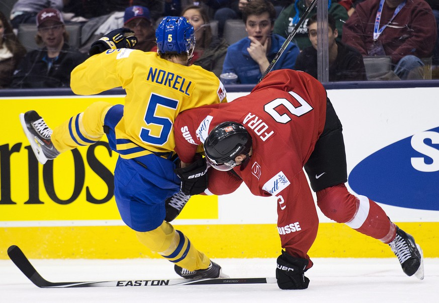 Sweden defenseman Robin Norell (5) collides with Switzerland defenseman Michael Fora (2) during the second period of a round-robin game at the world junior ice hockey championship in Toronto, Wednesday, Dec. 31, 2014. (AP Photo/The Canadian Press, Nathan Denette)