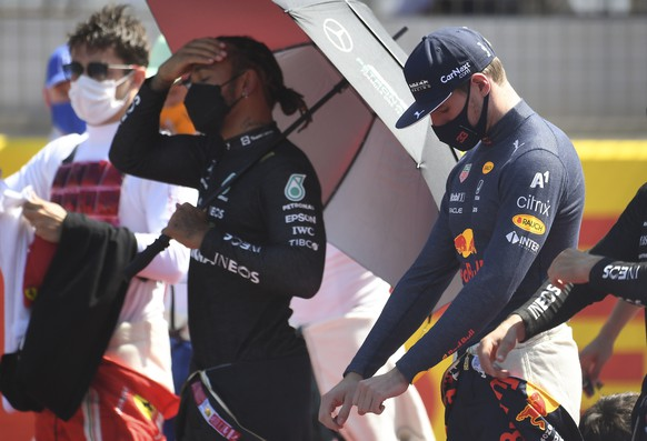 epa09351986 British Formula One driver Lewis Hamilton (C) of Mercedes-AMG Petronas and Dutch Formula One driver Max Verstappen (R) of Red Bull Racing prepare for the Formula One Grand Prix of Great Britain at the Silverstone Circuit, in Northamptonshire, Britain, 18 July 2021.  EPA/ANDY RAIN