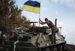 epa04368257 A soldier positions a Ukrainian national flag on an Armoured Personnel Carrier (APC) at a military camp, near the eastern Ukrainian town of Rassypnoe, 25 August 2014. Russia defied western criticism on 25 August by announcing that it will send a second aid convoy to areas in eastern Ukraine held by pro-Russian separatist rebels.  EPA/ROMAN PILIPEY