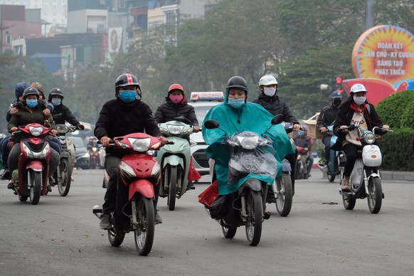 epa08970256 People wearing face masks ride motorbikes on a street in Hanoi, Vietnam, 28 January 2021. Vietnam reported its first two cases of COVID-19 disease community transmission in nearly two months, according to a report by the Ministry of Health.  EPA/LUONG THAI LINH