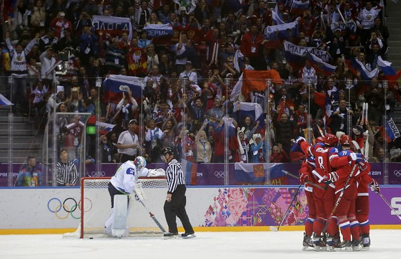 Fans cheer as Russia's Ilya Kovalchuk (71) is congratulated by teammates while Slovenia's goalie Robert Kristan (L) looks on during the second period of their men's preliminary round ice hockey game at the Sochi 2014 Winter Olympic Games February 13, 2014.  REUTERS/Mark Blinch (RUSSIA  - Tags: SPORT ICE HOCKEY OLYMPICS)