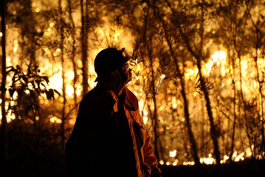 epa03914111 A New South Wales' RFS fire fighter looks at a bushfire burning close to homes on Patterson Street in Springwood in the Blue Mountains, west of Sydney, Australia, 17 October 2013. Media reports state that hundreds of houses may have been lost to forest fires in Australia's south-east, citing officials on 17 October. Crews battled to save homes without the help of fire-fighting aircraft, which were grounded because high winds and low visibility made flying too risky.  EPA/DAN HIMBRECHTS AUSTRALIA AND NEW ZEALAND OUT