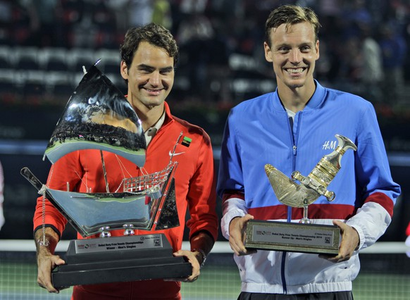 Roger Federer of Switzerland, left, and  Tomas Berdych of Czech Republic display their trophies after Federer  won the final match of the Dubai Duty Free Tennis Championships in Dubai, United Arab Emirates, Saturday, March 1, 2014. (AP Photo/Kamran Jebreili)