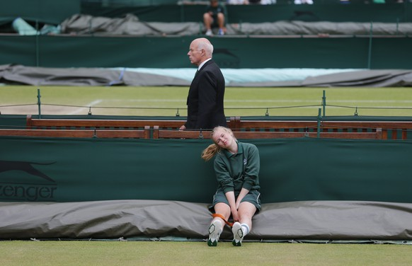 A female court coverer sits and waits for the signal to cover the court as showers skirt around Wimbledon on women's final day at the All England Lawn Tennis Championships at Wimbledon, London, Saturday July 5, 2014. (AP Photo/Ben Curtis)