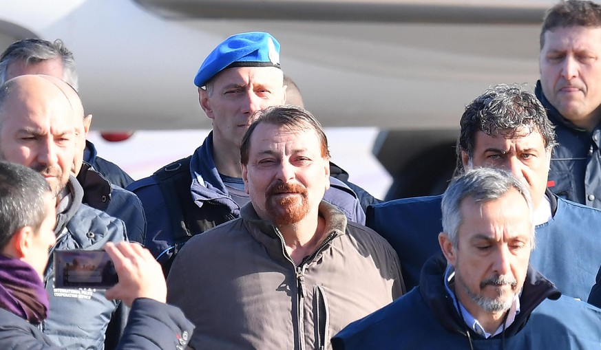 epa07282531 Former far-left militant Cesare Battisti (C) arrives escorted by Italian police at Rome's Ciampino airport, Italy, 14 January 2019. Cesare Battisti, 64, a former member of the far-left terrorist group Armed Proletarians for Communism (PAC), was arrested in Bolivia after 38-years as a fugitive of the Italian justice. He is set to serve a life sentence for four murders committed in Italy's 'years of lead' of political violence in the 1970s and 1980s, media reported.  EPA/ETTORE FERRARI