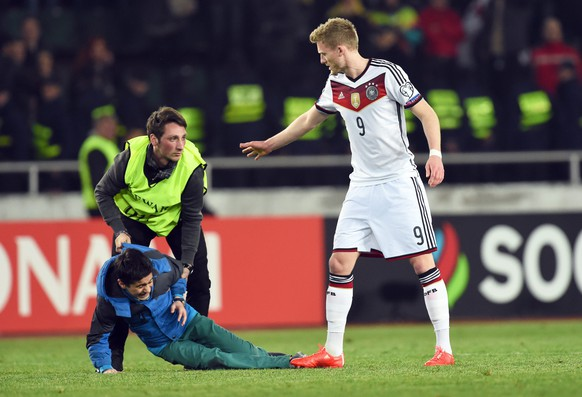 epa04685788 A pitch invader is caught by a steward next to Germany's Andre Schuerrle (R) during the UEFA EURO 2016 qualifying group D soccer match between Georgia and Germany in Tbilisi, Georgia, 29 March 2015. Germany won 2-0.  EPA/ARNE DEDERT
