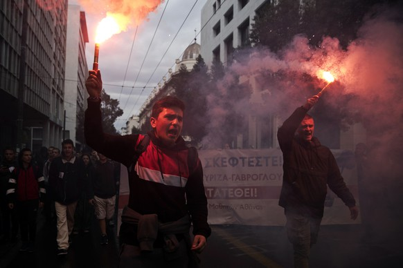 University students hold flares and chant slogans as they participate with striking teachers in a protest against planed education reforms in central Athens, on Friday, April 12, 2019.(AP Photo/Petros Giannakouris)