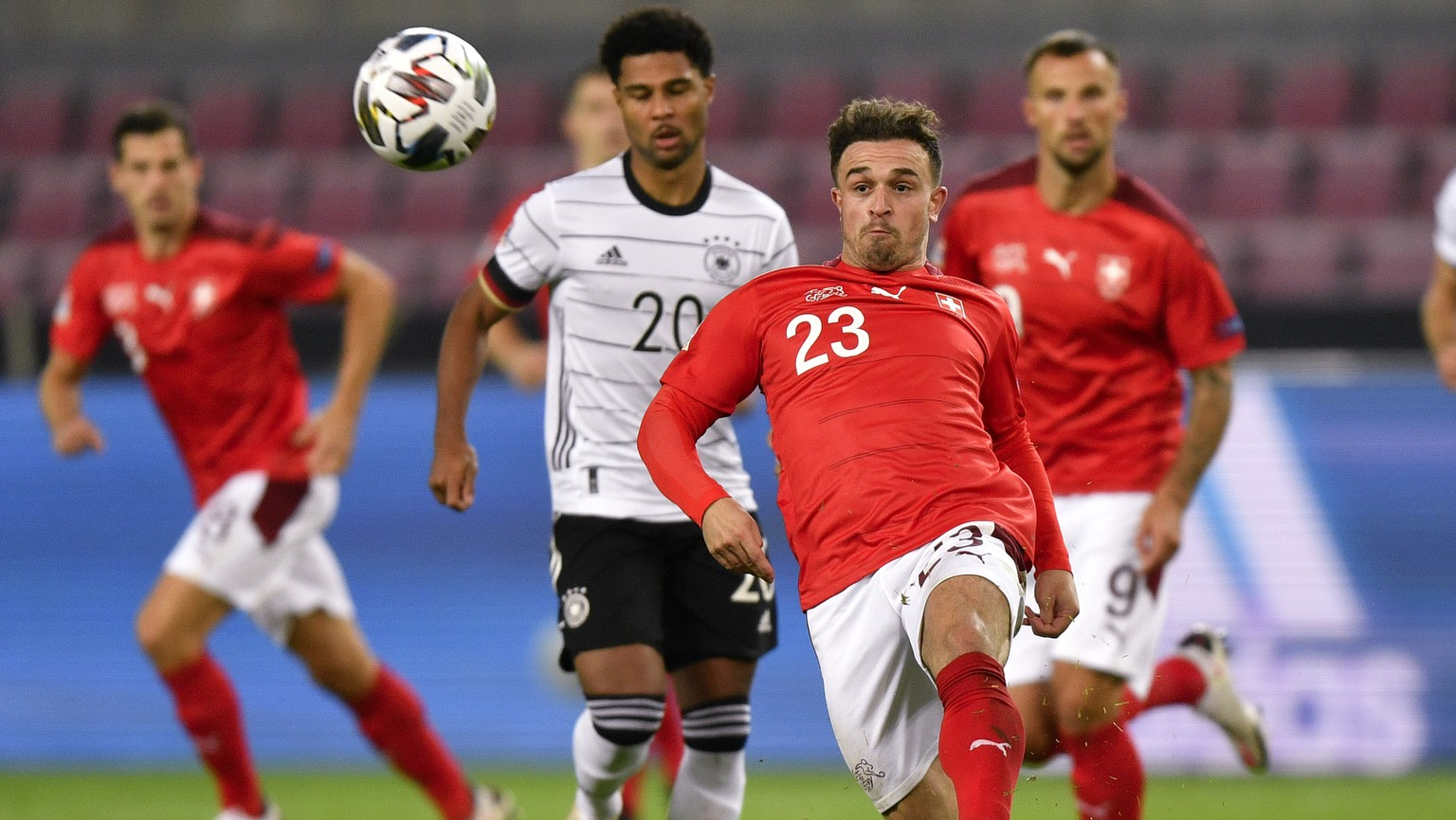 Switzerland's Xherdan Shaqiri kicks the ball away from Germany's Serge Gnabry during the UEFA Nations League soccer match between Germany and Switzerland in Cologne, Germany, Tuesday, Oct. 13, 2020. (AP Photo/Martin Meissner)