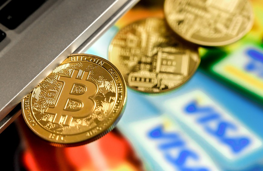 epa09018335 A bitcoin in a slot-in drive reflects in front of a monitor showing credit cards, in Duesseldorf, Germany, 17 February 2021. For the first time, the cryptocurrency Bitcoin has exceeded the mark of 50,000 dollars. Most recently, it became known that Elon Musk, CEO of the US electric car manufacturer Tesla, is said to have invested 1.5 billion dollars in Bitcoin. In recent weeks, he had boosted Bitcoin as well as other Internet currencies with positive news via the short message service Twitter. Credit card provider MasterCard also announced that it would open its payment network to cryptocurrencies. Visa plans to help banks introduce trading with Bitcoin and other cryptocurrencies by launching software with API access.  EPA/SASCHA STEINBACH