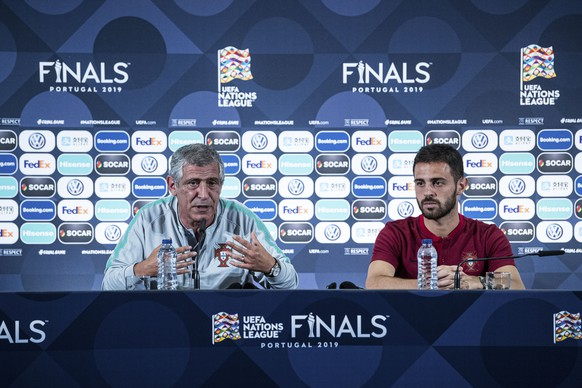 Portugal's Bernardo Silva, right, listens while Portugal coach Fernando Santos answers journalists during a news conference at the Dragao stadium in Porto, Portugal, Tuesday, June 4, 2019. Portugal will face Switzerland Wednesday in a UEFA Nations League semifinal soccer match. (Lukas Schulze/UEFA via AP)