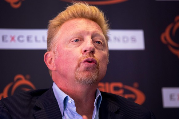 epa04724162 Former German tennis player Boris Becker speaks during a promotional event on a new bandage for athletes in Hamburg, Germany, 28 April 2015. Becker, currently working as coach of Serbian tennis player Novak Djokovic, is the co-developer and testimonial for the new sports bandage 'Magic Cooper'. The photo in the background shows Becker at a younger age.  EPA/CHRISTIANCHARISIUS