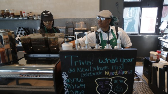 Baristas Mercedes Dillon, left, and Tay Winters prepare beverages at a Starbucks on South Claiborne Ave. in New Orleans, Thursday, Jan. 16, 2020. Starbucks, the home of the $4 latte, is expanding a program to open coffee shops in poor neighborhoods. The Seattle-based company plans to open or remodel 85 stores by 2025 in rural and urban communities across the U.S. Each store will have event space, and Starbucks will work with local United Way chapters to offer programs like youth job training. (AP Photo/Gerald Herbert)