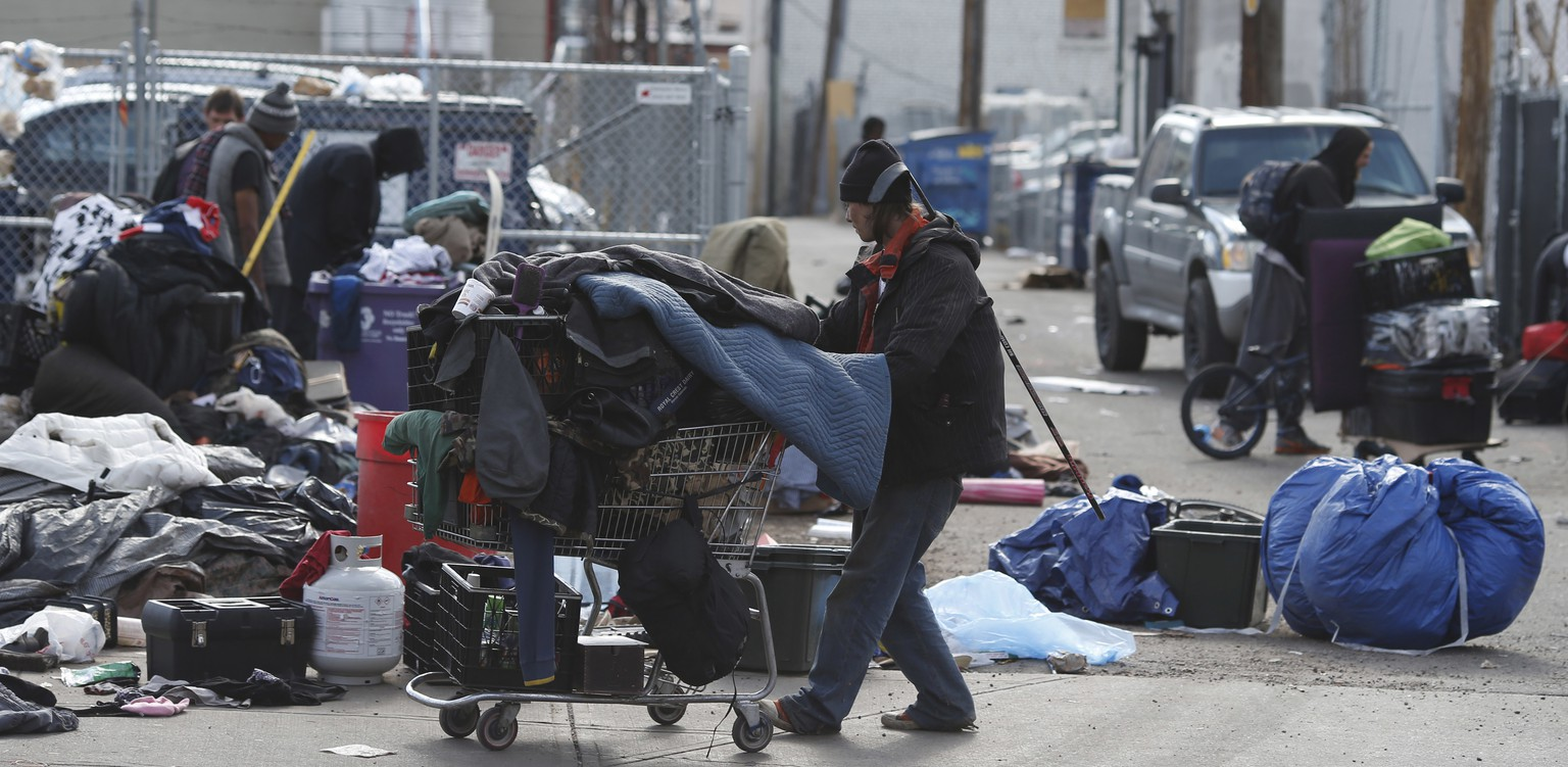 Homeless people clear their belongings of from a camp near the Denver Rescue Mission, Tuesday, March 8, 2016, in Denver. The city has spent months urging the campers to move into shelters and get rid of makeshift structures that officials say pose a health hazard. (AP Photo/David Zalubowski)