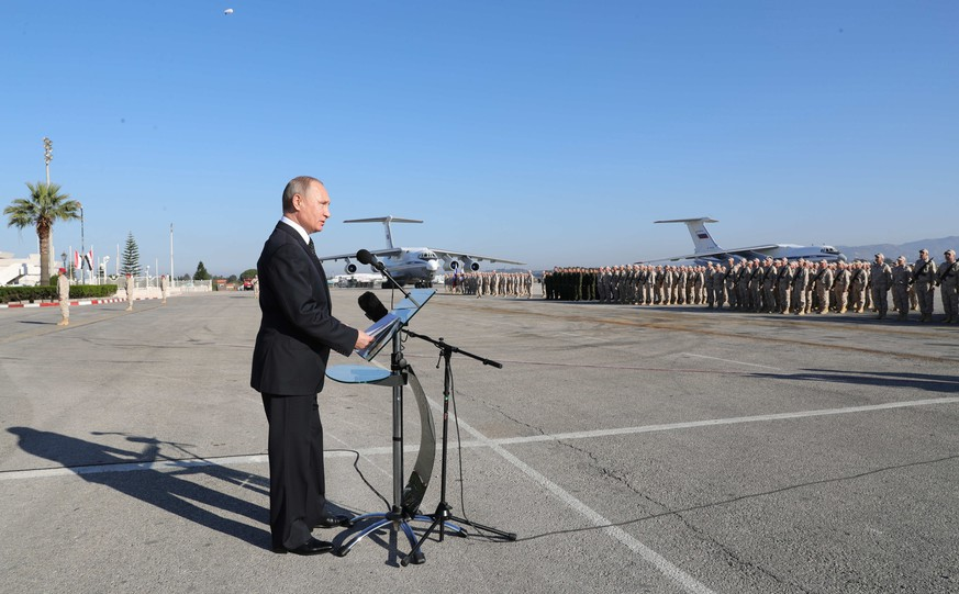 epa06382857 Russian President Vladimir Putin (L) visits the Hmeimim (also Khmeimim) Air Base, south-east of the city of Latakia in Syria, 11 December 2017. Media reports state Russian President Vladimir Putin made an unannounced visit to Syria where he met with Syrian Presidents Bashar al-Assad and ordered a withdrawal of Russian troops from Syria.  EPA/MICHAEL KLIMENTYEV / SPUTNIK / KREMLIN / POOL MANDATORY CREDIT
