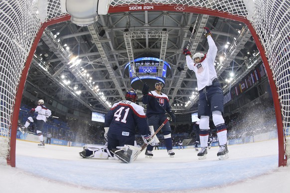 USA forward James van Riemsdyk celebrates John Carlson's goal in front of the Slovakia's goal as Slovakia goaltender Jaroslav Halak get up from his knees during mens' ice hockey game at the 2014 Winter Olympics, Thursday, Feb. 13, 2014, in Sochi, Russia. (AP Photo/Martin Rose, Pool)