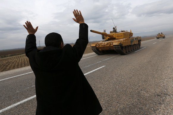 epa07078129 A man waves to Turkish soldiers on tanks near the Syrian-Turkish border, at Reyhanli district in Hatay, Turkey, 21 January 2018. Reports state that the Turkish army is on an operation named 'Operation Olive Branch' in Syria's northern regions against the Kurdish Popular Protection Units (YPG) forces which control the city of Afrin. According to YPG media channels, bombings by the Turkish military killed at least 10 people earlier on the same day. Turkey classifies the YPG as a terrorist organization.  EPA/SEDAT SUNA