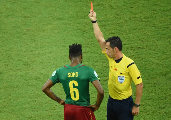 Portuguese referee Pedro Proenca Oliveira Alves Garcia (R) issues a red card to Cameroon's midfielder Alexandre Song (L) after a challenge on Croatia's forward Mario Mandzukic (out of frame) during the Group A football match between Cameroon and Croatia at The Amazonia Arena in Manaus on June 18, 2014, during the 2014 FIFA World Cup.  AFP PHOTO / EMMANUEL DUNAND
